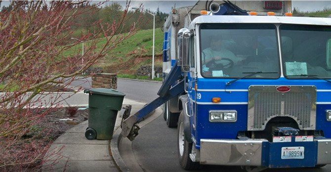 Truck Picking up a Trash Bin from the Sidewalk