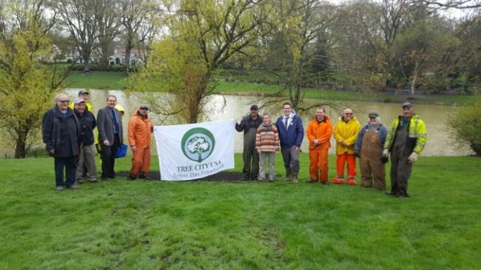 Urban Forestry Program Members Hold a Tree City U.S.A. Banner Next to a Pond