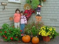 Two children pose with fall flowers and pumpkins