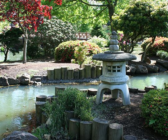 a Japanese garden with a cement lantern and river
